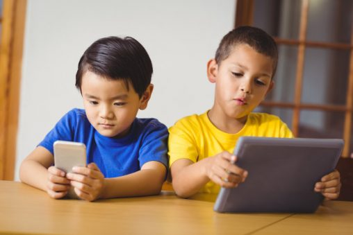 Cute pupils in class using phone and tablet at the elementary school
