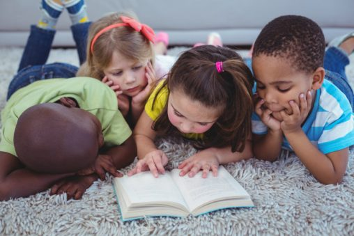 Happy kids reading a book together on the floor