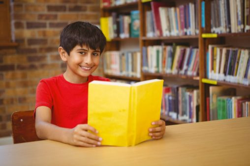 Portrait of cute little boy reading book in the library